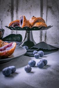 Blaubeer-Croissants, klassische Buttercroissants mit Blaubeerbutter, lila Croissants mit Blaubeer-Füllung / Blueberry croissants, classic butter croissants colored purple with blueberry butter and filled with blueberries [wienerbroed.com]