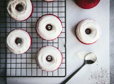 """Wer mir schon lange folgt, weiß, dass ich die """"traditionelle"""" Weihnachtsbäckerei immer meiner Mutter überlasse. Heute läute ich hier auf dem Blog aber auch die Weihnachtszeit ein, und zwar mit einem weihnachtlich anmutendem Rezept: Red Velvet-Donuts. Bei meiner Mutter gibt es Plätzchen aller Art. Von Feenküssen bis Hildabrötchen, diverse Sorten wandern ab Anfang November vom […]"""